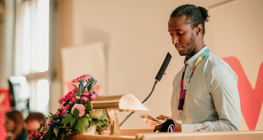 Sheikh seisoo puhujapöntössä pitämässä puhetta sisätilassa. Pitelee kännykkää kädessä, kukkia pöydällä.