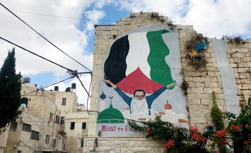 """Muraali, jossa teksti """"Resist to exist"""" ja henkilö pitelemässä Palestiinan lippua."""