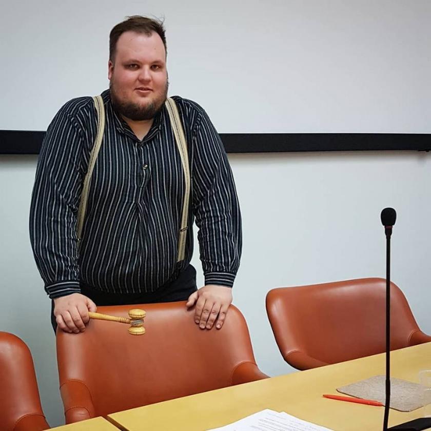 Miikka Kortelainen seisoo kokouspöydän takana kokousnuija kädessään.