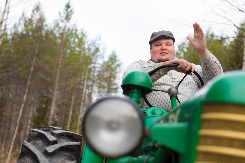 Valokuva iloisesti vilkuttavasta traktoria ajavasta Miikka Kortelaisesta.