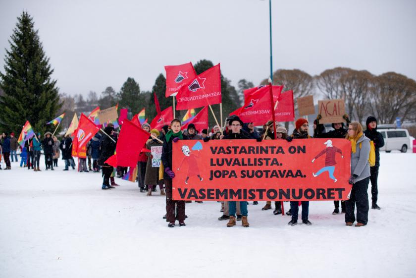 Mielenosoittavia vasemmistonuoria punalippujen kanssa talvimaisemassa.