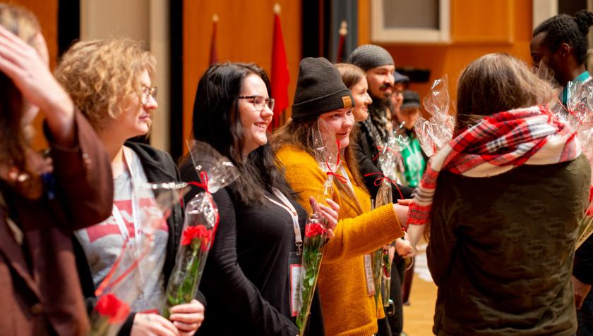 Hymyileviä nuoria seisoo sisätilassa rivissä. Kaksi henkilöä kättelee heitä ja jakaa heille kukkia.