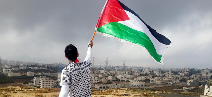 Henkilö heiluttaa palestiinalaislippua ilmassa, taustalla Miehitetyt palestiinalaisalueet.