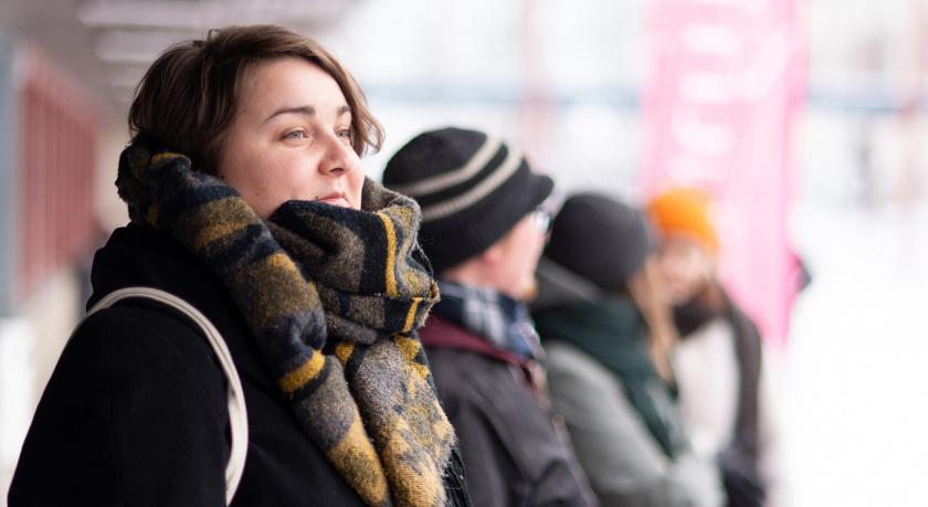Vasemmistonuoria seisoo ulkona talvella, henkilö hymyile..