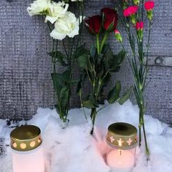 Kuva kynttilöistä ja kukista muistomerkillä.
