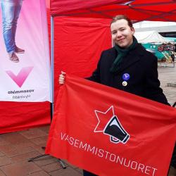 Waltteri Nummelin pitelee Vasemmistonuorten lippua vaaliteltan edessä.