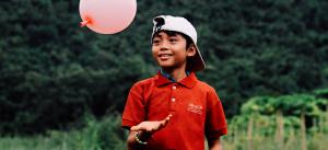 Lapsi hymyilee ja leikkii ilmapalloa.
