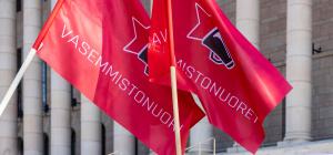Vasemmistonuorten kaksi lippua liehuu eduskuntatalon edessä