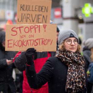 """Mielenosoitus talvella. Henkilö pitelee kylttiä, jossa lukee """"STOPPI! NYT ON EKOKATASTROFI""""."""