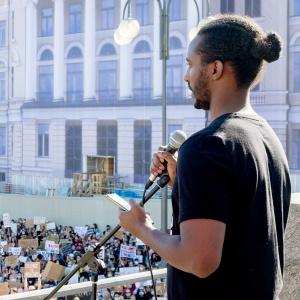 Sheikh seisoo ihmisjoukon edessä pitämässä puhetta Senaatintorilla. Aurinko paistaa.