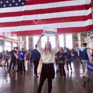 Vuorinen pitää käsissään kylttiä, jossa lukee Bernie, taustalla Yhdysvaltojen lippu