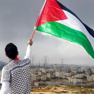 Henkilö heiluttaa palestiinalaislippua ilmassa, taustalla Miehitetyt palestiinalaisalueet