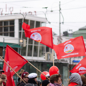 Helsingin vasemmistonuoret vappumarssilla. Punaiset liput liehuvat Lasipalatsin edessä.