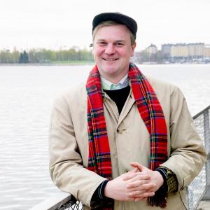 Valokuva hymyilevästä Joonas Pulkkisesta. Nojaa kaiteeseen meren rannalla.