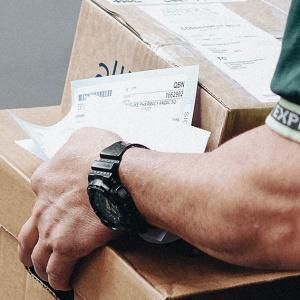 Valokuva postityöntekijästä kantamassa paketteja.