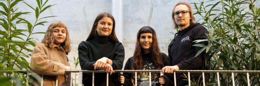 Neljä nuorta nojaavat aitaan ja hymyilevät kameralle