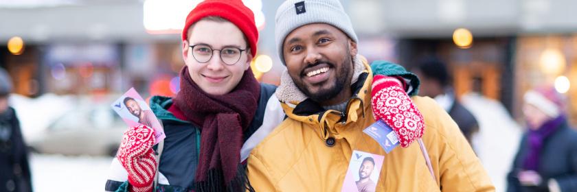 Kaksi hymyilevää henkilöä jakaa flyereita kadulla talvella
