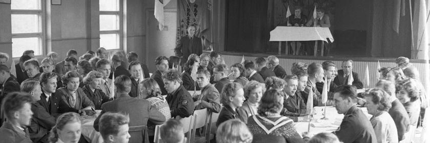 Mustavalkoinen valokuva ihmisistä istumassa pöytien ääressä salissa.