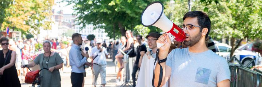 Mielenosoitus kävelykadulla. Henkilö huutaa megafoniin. Ihmiset pitävät banneria ja taustalla toimittaja puhuu mikrofoniin.