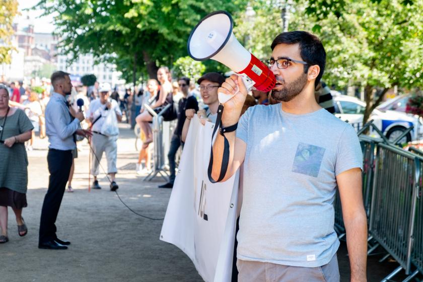 Henkilö huutaa megafoniin, taustalla banderolli