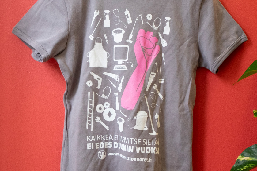 """T-paita, jonka rinnassa """"Kaikkea ei tarvitse sietää - ei edes duunin vuoksi"""" -teksti ja piirrettyä työkaluja ja muita työelämään yhdistettäviä esineitä."""